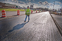 A construction worker walks over a roadway recently sprayed with tart as they lay asphalt on Westerville Road at Dempsey as roadway improvements near completion at the intersection. The changes are part of an improvement project at the I-270 interchange to upgrade the entrance road to Westerville, OH.