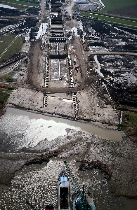 Nederland, Zuid-Holland, Oude Maas, 08-03-2002; HSL: constructie Zuidelijke toerit en tunnel onder de Oude Maas (in Z richting, naar Hoeksche Waard); baggerschepen (voorgrond) zijn begonnen met het uitbaggeren van de geul waar de tunnelelementen ingevaren zullen worden (zie ook Bouwdok), deze geul loopt tot ongeveer twee derde (tot zijweg naar rechts van modder), daarna begint de eigenlijke toerit .infrastructuur verkeer en vervoer spoor bouw;<br /> luchtfoto (toeslag), aerial photo (additional fee)<br /> foto /photo Siebe Swart