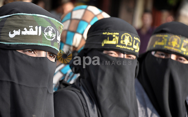 Female member of al-Quds brigades, the military wing of Jihad Islamic organisation take part in a march along the streets in Gaza City on November 13, 2013, ahead of the first anniversary an Israeli army operation which was launched after the killing of top Palestinian military commander Ahmed Jaabari in an air strike. The November 2012 fighting between Israel and Palestinian militants in the Gaza Strip lasted one week and costed the lives of at least 136 Palestinians and five Israelis. Photo by Mohammed Talatene