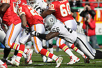 Oakland Raiders DE Derrick Burgess tackles Chiefs RB Larry Johnson in the first quarter at Arrowhead Stadium in Kansas City, Missouri on November 19, 2006. Kansas City won 17-13.