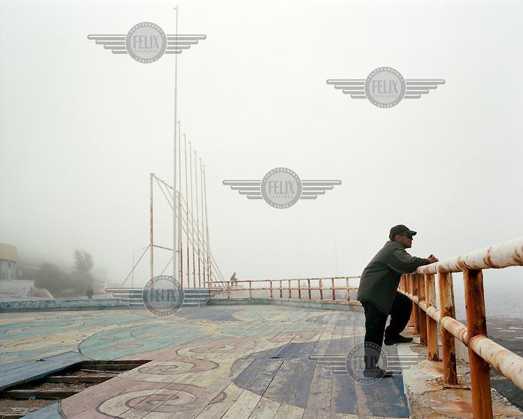 A man looks out at the Caspian Sea on Aktau's rusting promenade.