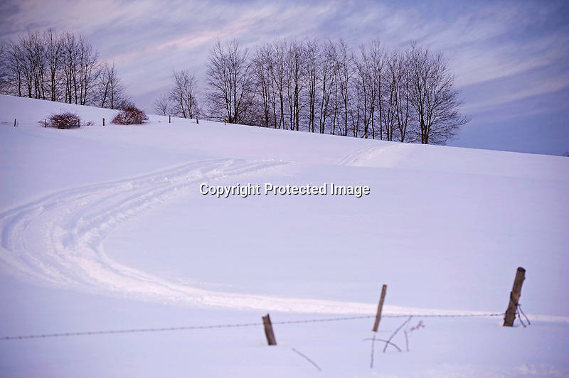 Snowmobile Track Running across a Snowy Pasture Hill in Wintry New Hampshire