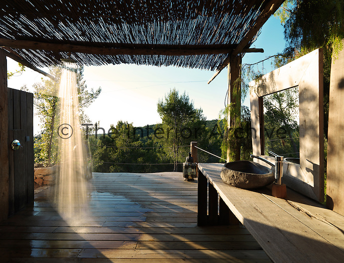 An outdoor shower room is open to the elements, sheltered only by the bamboo roof of the terrace