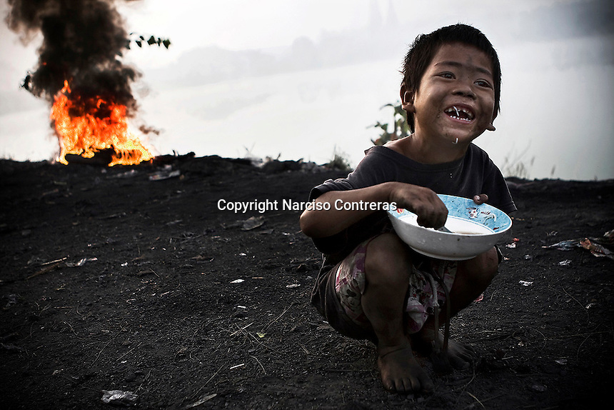 Burmese refugee child s getting a breakfast at the rubbish dump in the bordertown of Mae Sot, Thailand.