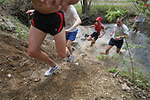 Runners cross over one of many creeks during the 15k trail run, at the Mount Penn Mudfest on Saturday April 15, 2006 in Reading, Pa. Usually the race is very muddy, with creek crossings and with April being a rainy month, however, the run was not as muddy as expected the only thing water logged were feet. Jane Therese For The New York Times.