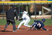 Nathan Aide (29) of the Illinois Fighting Illini slides into second base ahead of the tag by Brian Port (5) of the Coastal Carolina Chanticleers as umpire Gary Swanson looks on at Springs Brooks Stadium on February 22, 2020 in Conway, South Carolina. The Fighting Illini defeated the Chanticleers 5-2. (Brian Westerholt/Four Seam Images)