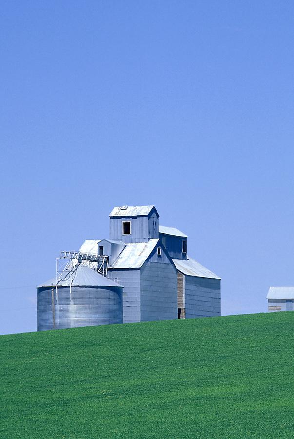 Grain silos and wheat field below blue sky, Palouse area, Washington.