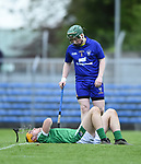 Clare's Killian Nugent looks on at an Injured Brian Ryan of Limerick during their Munster U-21 hurling quarter final at Cusack park. Photograph by John Kelly.