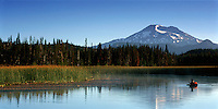 Distant view of a fly fisherman on Hosmer Lake in a forest and mountain landscape. Oregon.