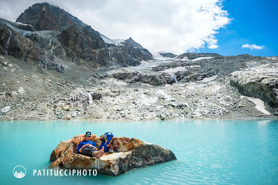 A climber relaxes on a rock in a turquoise mountain lake beneath the 4357 meter Dent Blanche, Switzerland.