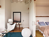 The bedroom area and sitting areas are separated by a sliding door. The neutral decoration creates a light and airy feel to the space with spots of colour provided by the blue and yellow rugs.