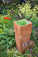 A square ceramic terra cotta urn cames alive with a little green paint and sets off the shade garden alongside oriental poppies, maroon barberry and varigated comfrey in Dan Johnson's Denver garden..