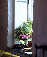Detail of a jug of fresh peonies on a window sill surrounded by piles of wooden bowls