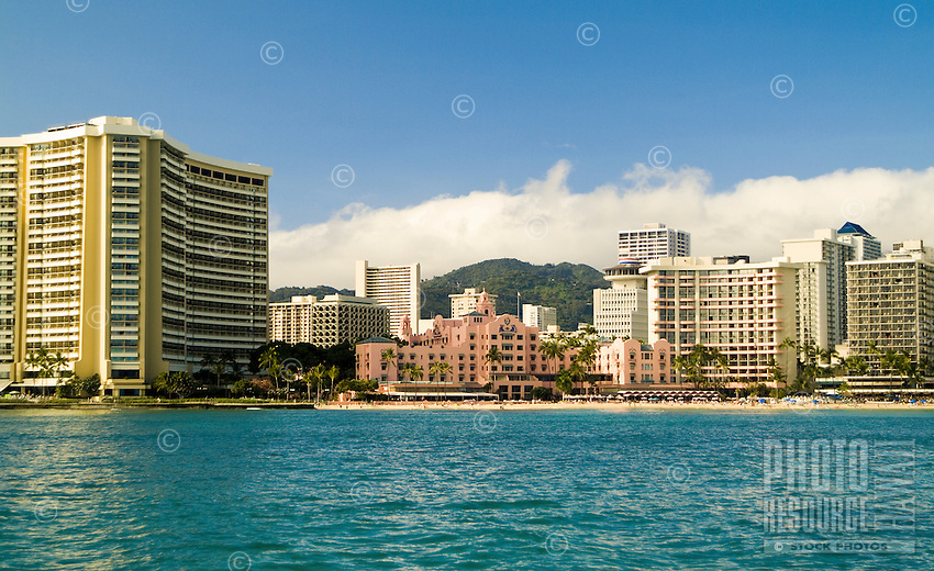 The Sheraton Waikiki and Royal Hawaiian Hotel with clear blue water in the foreground as seen from a sailboat off Waikiki