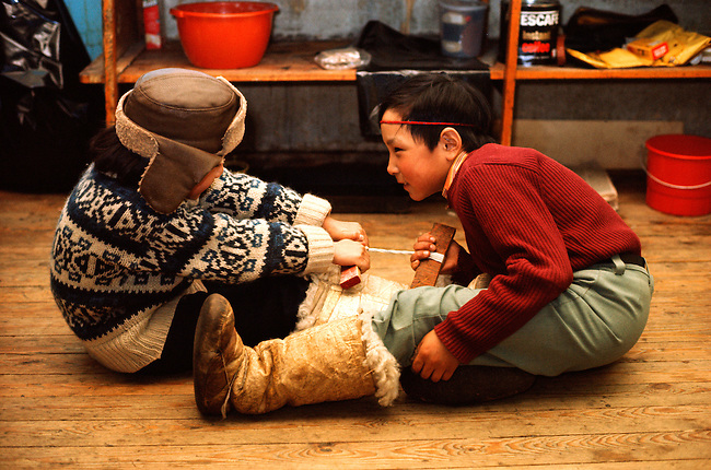 Inuit boys playing a traditional tug-of-war game, seated on the floor. Siorapaluk. NW Greenland.