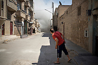 A man peers down a street as dust rises from a residential home destroyed by a bomb dropped from a Syrian Airforce fighter jet that was targeting the neighbouring Free Syrian Army (FSA) command centre in Aleppo. Eleven civilians from two families died including at least four children.