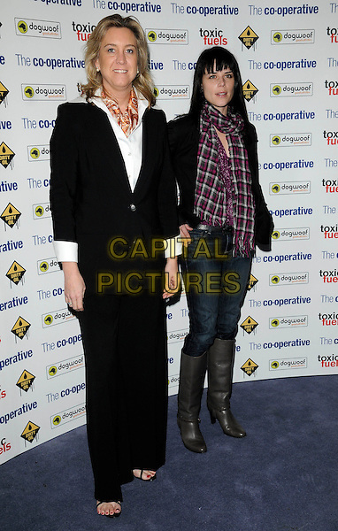 "LESLIE IWERKS & NEVE CAMPBELL .The film premiere of ""Dirty Oil"", Barbican Centre, London, England.March 15th 2010.full length black jacket red pink checked check scarf gingham plaid fringe jeans grey gray knee high boots denim trousers suit white shirt .CAP/CAN.©Can Nguyen/Capital Pictures."