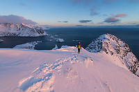 Female hiker on winter hike of Reinebringen, Moskenesøy, Lofoten Islands, Norway