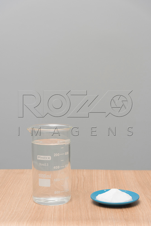 Béquer com mistura de água e sal e prato com sal, 2017.