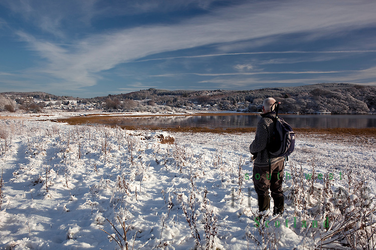 Winter walking snow walker admiring the view near Glen Isle looking across the River Urr to Kippford on the Solway Firth coast Dumfries and Galloway Scotland UK