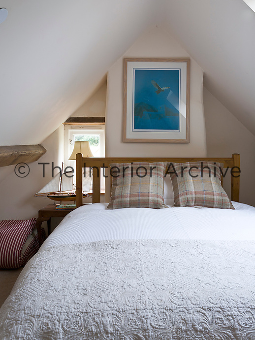 A contemporary turquoise print adds a dash of colour to this attic bedroom