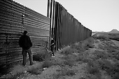 Agua Prieta.Mexico.October 22, 2006..A young Mexican man and woman look through holes in the fence in hopes of jumping over it to enter the city of Douglas in the USA illegally in the very early morning hours.