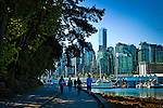 People walking along the waterway, Stanley Park, Vancouver, B.C, Canada on a sunny day, early summer. Backdrop of many windowed skyscrapers.