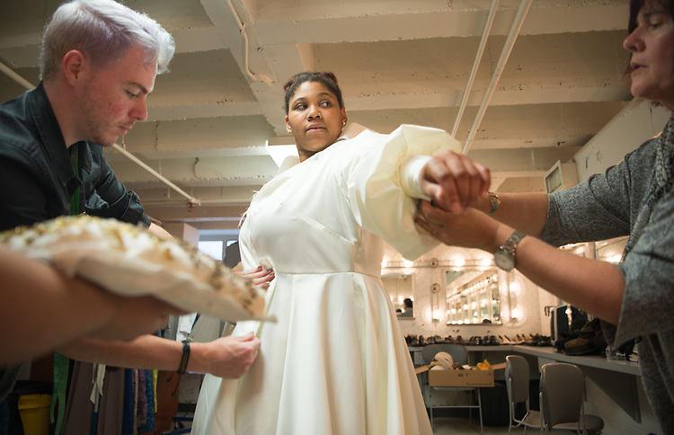 """Kenneth Rainey (Left) and Julie McGill (Right) fit a dress for actress Mariah Burks in preparation for, Caroline, or change"""" at the Tantrum Theater. Photo by Ben Siegel"""