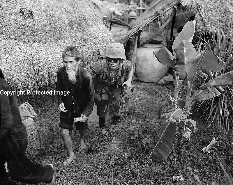 Vietnam - 08/03/1965-<br /> ....A Marine from 1st Battalion, 3rd Marines, moves a Viet Cong suspect to the rear during a search and clear operation held by the battalion 15 miles west of Da Nang Air Base.
