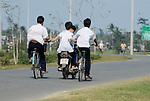 Asia, Vietnam, nr. Hoi An. Vietnamese school boys on their way home.