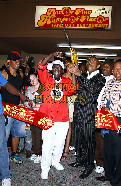 Flavor Flav (William Jonathan Drayton, Jr.).Grand Opening of Flavor Flav's House of Flavor Take Out Restaurant, Las Vegas, Nevada, USA..March 15th, 2012.full length orange top white trousers giant oversized scissors cut cutting ribbon arms in air hat baseball cap hat .CAP/ADM/MJT.© MJT/AdMedia/Capital Pictures.