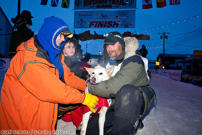 Rookie musher Chris Adkins poses with his lead dog, his daughter Kristina and his dad, Terry Adkins who was the first volunteer veterinarian, at the finish line in Nome during the 2010 Iditarod