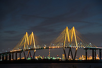 Fred Hartman Bridge at Night -  Fred Hartan bridge after dark with the lights on giving it a golden glow against the night sky.  The bridge span 2.8 miles across the ship channel from  La Porte to Baytown Texas.  This is cable stay bridge and it is the largest in Texas out of only four other similar stay bridges.  The Fred Hartman bridge is 77th largest in the nation.  The bridge was built to replace the Baytown tunnel that went underneath the water so they could dig it out for bigger ships to pass.  I remember going through the tunnel when I was a kid always worried that it would collapse as we went through.  You can cleary make out all the refinery lights from  underneath the bridge even the fracking flares.  This is the energy sector which is near the Port of Houston with refineries in every direction you look.
