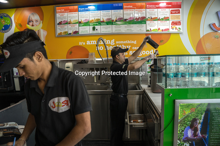 30 year old Haidar Ali (right), a deaf employee makes juice for a customer at Joost, a juice bar in a fitness club in New Delhi, India.