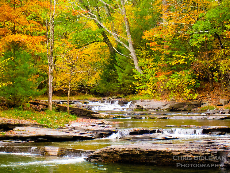 Fall color in the trees is seen with a river cascading from rock to rock to form many small waterfalls in the Catskill Mountains of Upstate New York.