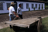 Sao Paulo State, Brazil. Colonial Ranch (Fazenda) with an antique wooden bullock cart and two ranch hands.
