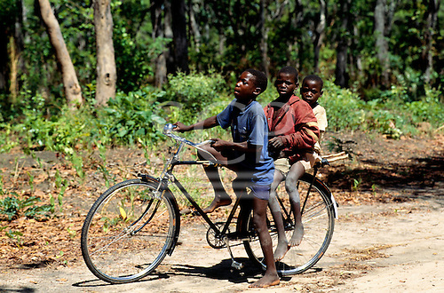 Chitimba, Zambia. Three boys on a bicycle at the side of a dirt road.