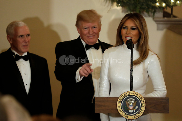 United States President Donald J. Trump gestures behind First Lady Melania Trump as US Vice President Mike Pence looks on at the Congressional Ball at White House in Washington on December 15, 2018. <br /> Credit: Yuri Gripas / Pool via CNP / MediaPunch