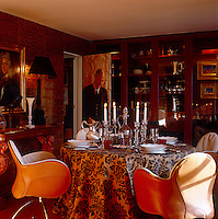 Leather saddle chairs by Vico Magistretti surround the dining table and a photo of a butler covers the door leading to the kitchen