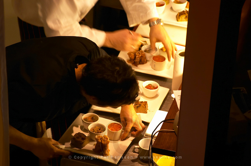 The food being prepared in the kitchen before being served to guests at the restaurant CRU in Montevideo, supposedly one of the better and trendier restaurants in the city. The chef is putting finishing touches on the plates. Montevideo, Uruguay, South America