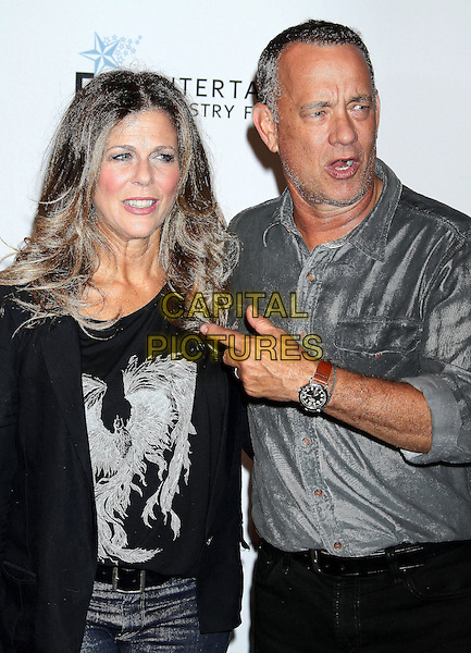 Rita Wilson, Tom Hanks <br /> at The Shakespeare Center of Los Angeles' 23rd Annual Simply Shakespeare held at The Broad Stage, Santa Monica, California, USA, 25th September 2013.<br /> half length husband wife couple grey gray striped shirt black t-shirt jacket  phoenix print hand finger pointing gesture mouth open <br /> CAP/ADM/RE<br /> &copy;Russ Elliot/AdMedia/Capital Pictures