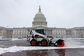 A architect of the United States Capitol staff member uses a Bobcat to clear snow from the United States Capitol plaza on a snowy afternoon in Washington, D.C. on March 21, 2018. Credit: Alex Edelman / CNP