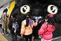 Passersby caress a big cat face on display in Shibuya station on April 5, 2015, Tokyo, Japan. The Japanese courier service Yamato Transport Co., LTD. is using this innovative display to promote its two new services for small packages from April 1st. (Photo by Rodrigo Reyes Marin/AFLO)