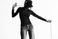 Female standing while puling the cord of headphones in pinstripe Jeans and a slim fitting long-sleeve top