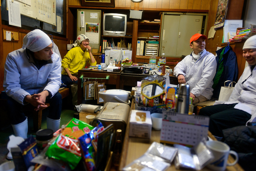"(left to right) Tsuji Soichiro, Tsuji Makiko and brewery workers during a break time. Tsuji Honten Sake, Katsuyama town, Okayama Prefecture, Japan, February 1, 2014. Tsuji Honten was founded in 1804 and has been at the cultural centre of the town of Katsuyama for over two centuries. 34-year-old Tsuji Soichiro is the 7th generation brewery owner. His elder sister, Tsuji Maiko, is the ""toji"" master brewer."