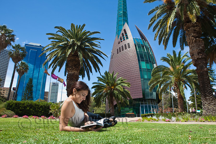 Young woman reading a book in a park with the Swan Bell Tower in the background.  Perth, Western Australia, Australia