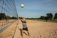 Man playing volleyball returns the ball under a clear blue sky on a perfect summer's day at the Zilker Park sand volleyball courts.