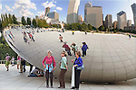 Three mature females pose in comical poses at Anish Kapoor's Cloud Gate sculpture in Millenneum Park in Chicago, Illinois