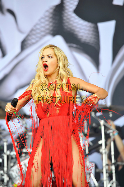 Rita Ora <br /> performing at Glastonbury Festival, Worthy Farm, Pilton, Somerset, <br /> England, UK, 28th June 2013.<br /> live on stage music gig half red tassels dress hotpants microphone black pants fringed singing mouth open funny arms <br /> CAP/MAR<br /> &copy; Martin Harris/Capital Pictures