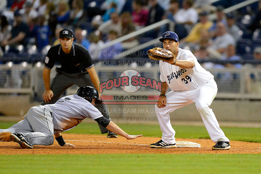 Pensacola Blue Wahoos first baseman Donald Lutz #39 takes a throw as Daniel Pertusati #2 dives back with umpire Ryan Goodman looking on during a game against the Jacksonville Suns on April 15, 2013 at Pensacola Bayfront Stadium in Pensacola, Florida.  Jacksonville defeated Pensacola 1-0 in 11 innings.  (Mike Janes/Four Seam Images)